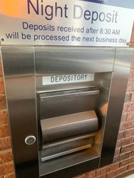 A secure night depository mechanism placed on the wall of a bank in vertical image format.