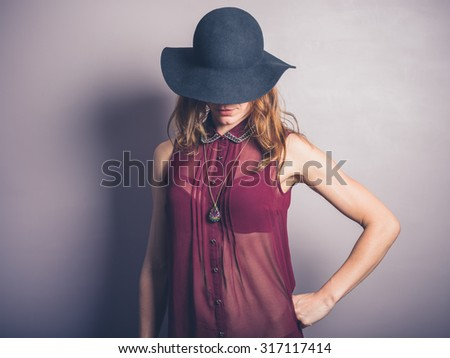 A seductive young woman is wearing a hat and a transparent shirt #317117414