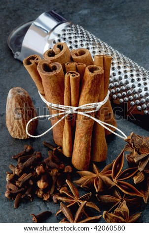 A selction of whole spices used in mulled / spiced hot wine - cinnamon, cloves, nutmeg and star anis with a stainless steel nutmeg grater