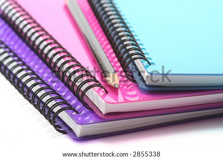 A selection of brightly coloured spiral bound notebooks with pencil