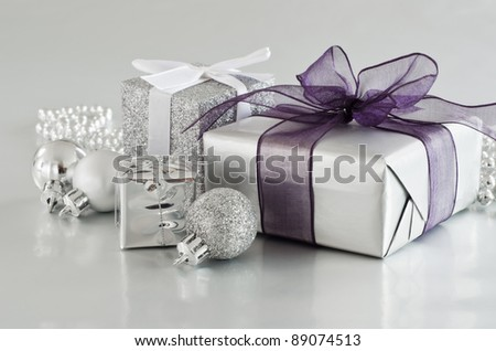 A selection of Christmas gifts and ornaments in silver, on a silver reflective surface.