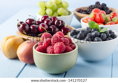 A selection of different Summer fruits, in a variety of bowls on a painted blue wood planked farmhouse kitchen table, against a light blue background.