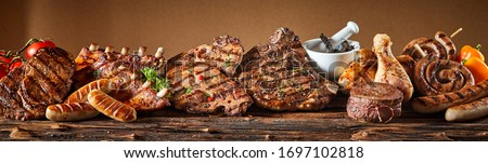 A selection of grilled gourmet meats on a rustic timber board.