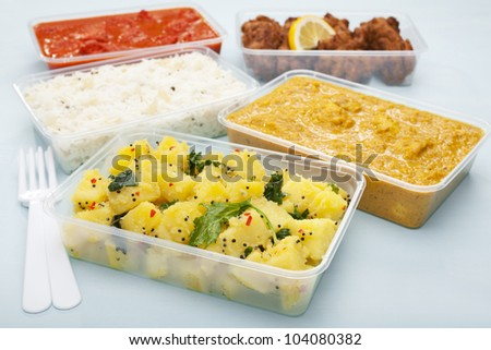 A selection of Indian takeaway food in plastic containers. Aloo saag (potato spinach curry), chicken tikka masala, chicken bhoona or  bhuna, basmati rice and onion bhaji or pakora.