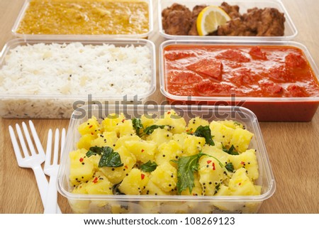 A selection of Indian takeaway food in plastic containers on a wooden table. Aloo saag (potato spinach curry), chicken tikka masala, chicken bhoon or  bhuna, basmati rice and onion bhaji or pakora.