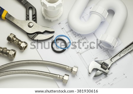 A selection of plumbing tools and fittings on house plans