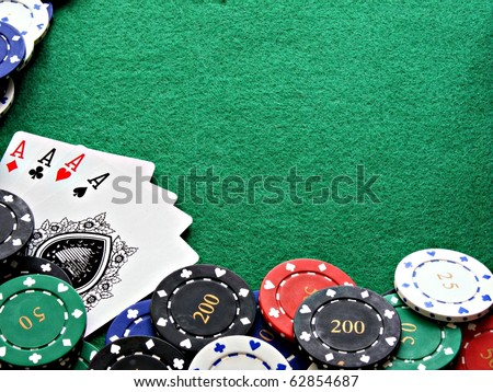 A selection of poker chips with 4 aces on a green felt background