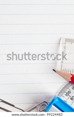 A selection of stationery bordering the bottom and right side of a lined paper background from a school exercise book.