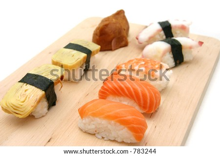 A selection of sushi served on a wooden surface board