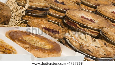 A selection of sweet pastry pies and tarts for sale on a market stall
