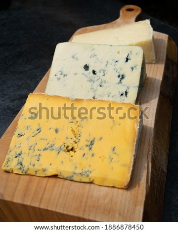 A selection of three cheeses on a wooden platter on an outdoor table in Cartmel, Cumbria Stock photo ©