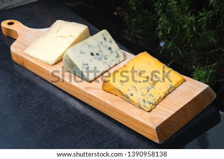 A selection of three different cheeses on a platter in Cartmel at the cheese shop garden Stock photo ©