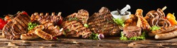 A selection of various barbecued gourmet meats on a rustic timber board with a black background.