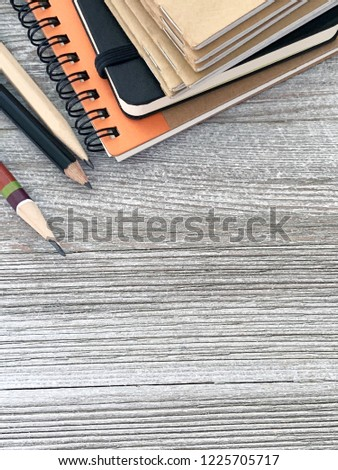 A selection of wire-bound, staple-bound, rubber-bound pocket notebooks along with pencils in extenders set on planks of white painted board.