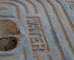 A selective focus abstract image of an old  rusty water meter plate dug out of the ground in Madisonville, Louisiana.