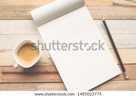 A selective focus of a blank sketchbook placed on a wooden top of table with a pencil and a cup of espresso.