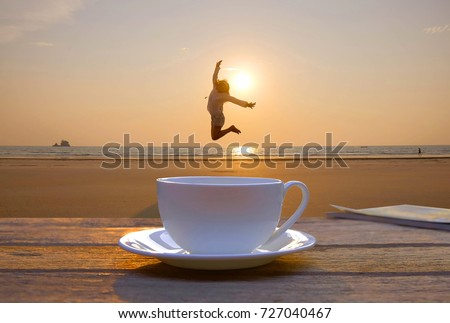 a selective focus picture of a cup of coffee on wooden table in the morning sunrise at public beach in the South of Thailand