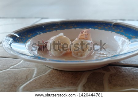 """A selective focus picture of squid been cut and serve as """"ketupat sotong"""" or sticky rice in squid."""