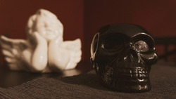 A selective focus shot of a black skull sculpture with a blurred white angel background