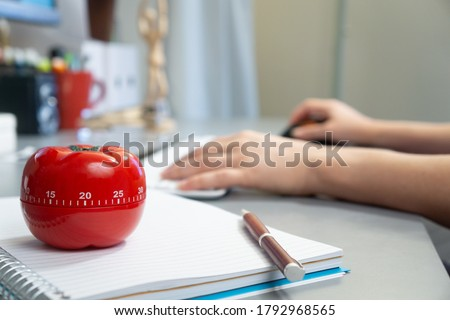Photo of  A selective focus shot of a kitchen timer in the form of a tomato on a notebook with a female working on her computer in the background