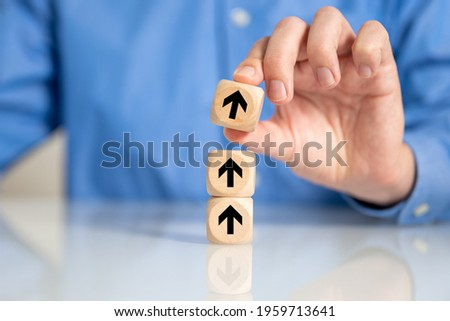 A selective focus shot of a male's hand arranging wooden blocks with arrow going up sign-concept for business growth process Photo stock ©