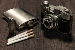 A selective focus shot of a vintage camera, a flask, cigarettes, and a cigarette lighter on a table