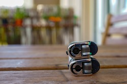 A selective focus shot of two stacked lighters on a wooden surface