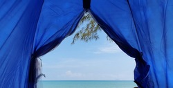 A selective photo by a scenary view from a tent. Camping beside a beach.