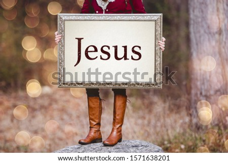 "A selective shot of a person holding a picture frame with word ""Jesus"" written as a text"
