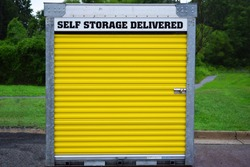 A self storage pod or shed with a yellow door and lock. Sign indicates a deliverable self-storage unit. Unit is on a street or parking lot with green grass and trees in background. Outdoors in daytime