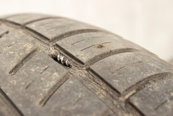A self-tapping screw is removed from the wheel tire. A self-tapping screw with a thread lies on the tire next to the punctured hole.