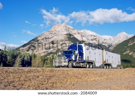 a semi truck going up through the Canadian Rockies with motion blur