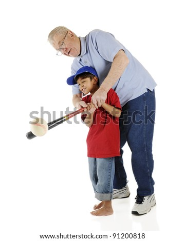 A senior and his preschool grandson working together to successfully bat a baseball.  On a white background.