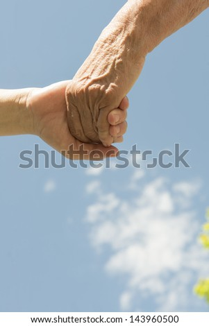A senior and women holding hands under a blue sky with clouds