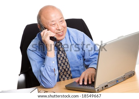 A senior asian businessman talking on the phone while working on his laptop