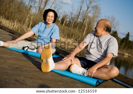 A senior asian couple stretching before exercise - stock photo