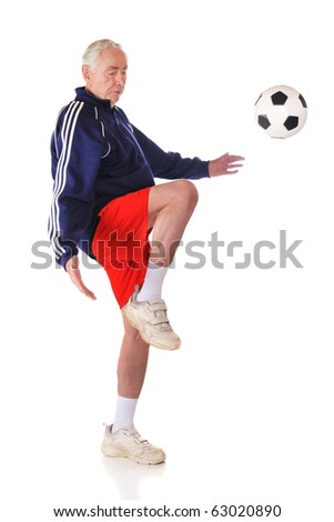 A senior athlete kneeing a soccer ball.  Isolated on white.