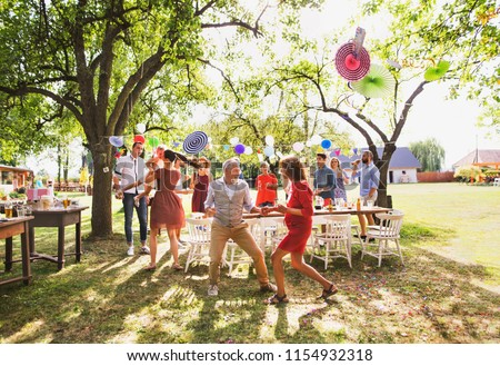 A senior couple and family dancing on a garden party outside in the backyard. #1154932318
