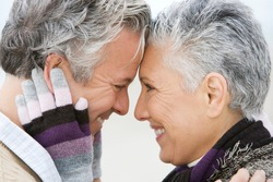 A senior couple embracing wearing gloves