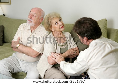 A senior couple in marriage counseling.  They have their backs turned and are ignoring each other while the therapist tries to reconcile them.