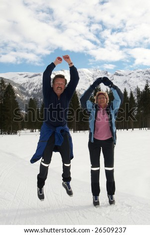 A senior couple outdoor in a winter setting. The couple jumps in the air. Slight motion bluriness is intend.