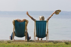 A senior couple relaxing in deckchairs beside a lake