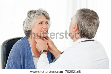 A senior doctor doing an examination of his patient in his office - stock photo