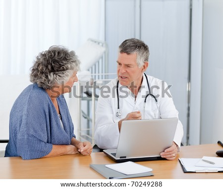 A senior doctor with his patient looking at the laptop in his office