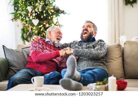 A senior father and adult son sitting on a sofa at home at Christmas time, laughing. #1203023257