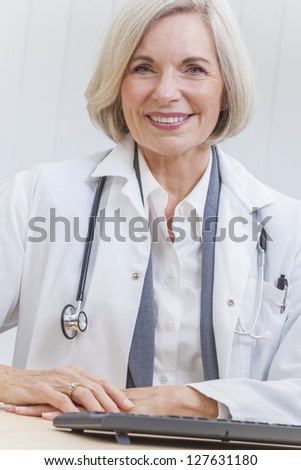 A senior female doctor sitting at a desk in an office with a computer, wearing a suit and stethoscope