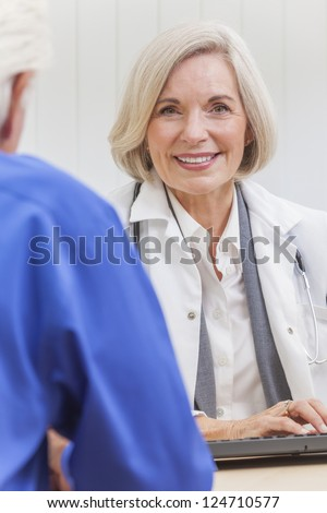 A senior female woman doctor sitting at a desk wearing a suit and stethoscope talking to an elderly male patient