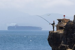A senior fisherman stands on a rock on the Strait of Gibraltar near the city of Tarifa. Seagulls are in the air. A large container ship passed. On the horizon are the mountains of Morocco.