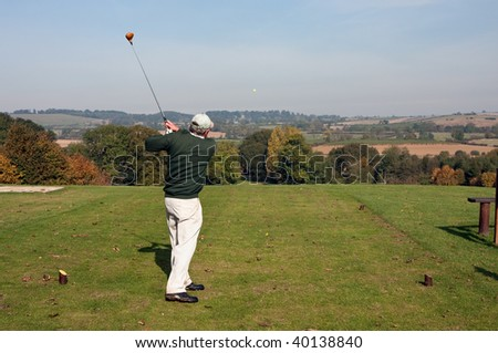 A senior golfer teeing off with a driver from an elevated tee in early autumn. Yellow ball, with tee shot heading straight down the fairway.