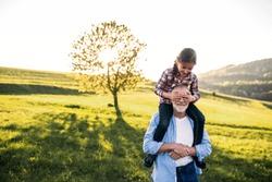 A senior grandfather giving a small granddaughter a piggyback ride in nature.